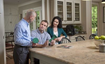 Homeowners at a kitchen table with a Pest Professional