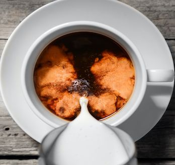 cup of coffee with cream being added - view from above