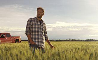 Farmer in field in front of red truck
