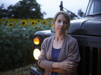 Woman standing infront of a truck parking infront of a field of sunflowers