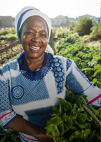 Smiling female farmer holding crops