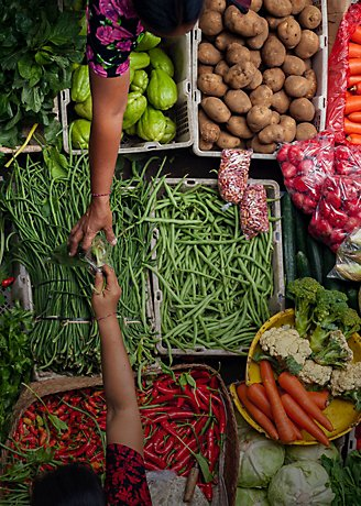 Arms reaching across market vegetables