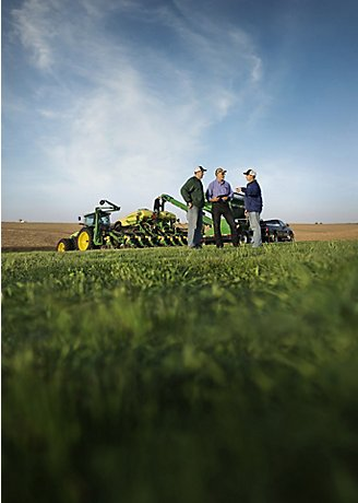 Men talking by planter in field