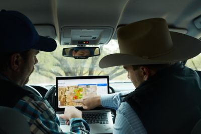 Two people reviewing LandVisor on a laptop.
