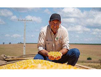 Homem olhando para a câmera e agachado em cima de um caminhão de sementes, sugurando sementes de milho na mão.