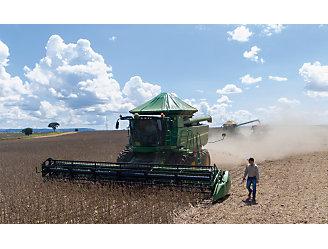 Colheitadeira fazendo a colheita de soja enquando um homem acompanha do lado.