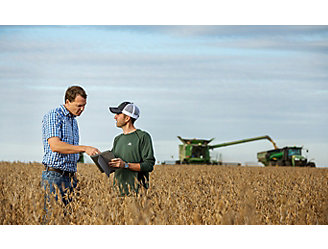 Representative and farmer talking in soybean field
