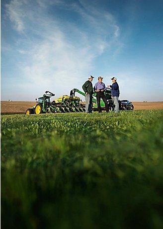 Men talking by planter in field