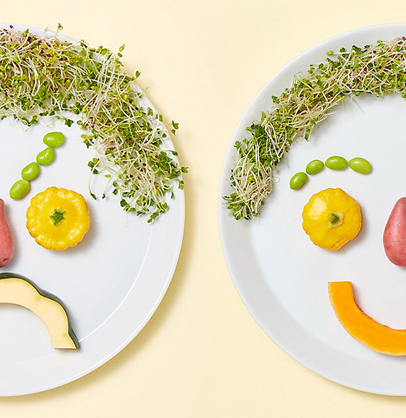 Two plates using various fruits and vegetables to depict faces. One face is frowning, and the other is smiling.
