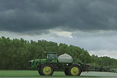 Sprayer in field spraying with dark clouds in background