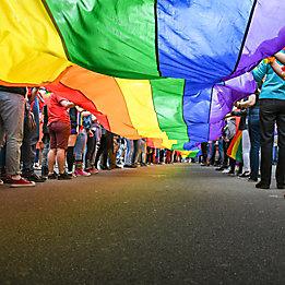 Хора държат флага на прайд движението.