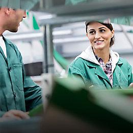 Двама работници във фабрика с усмивка