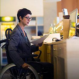Жена в инвалидна количка пред компютър