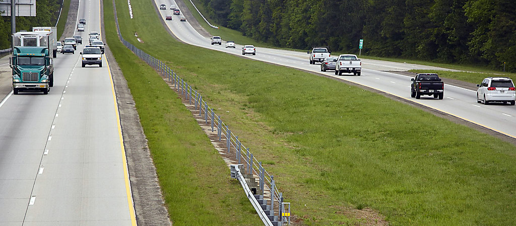 Image of two highways divided by grass, with cars and trucks driving