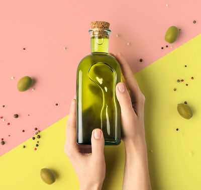 Hands holding a bottle of olive oil with olives surrounding the hand.