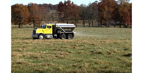 Truck applies impregnated fertilizer to field.