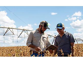 Dois homens de boné no meio de uma lavoura de soja olhando para a tela de um tablet.