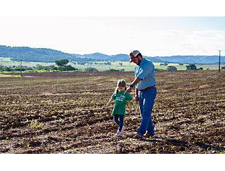 Pai e filha andando pelo campo.