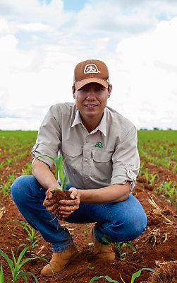 Homem olhando para a câmera ajoelhado no meio de uma lavoura de milho recém plantada, segurando uma planta pequena de milho.